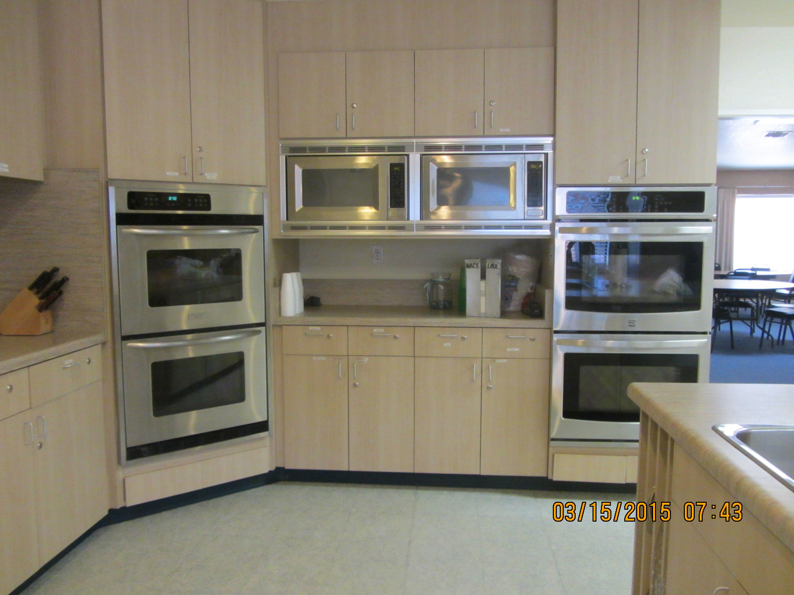 kitchen showing both industrial size ovens and cabinets